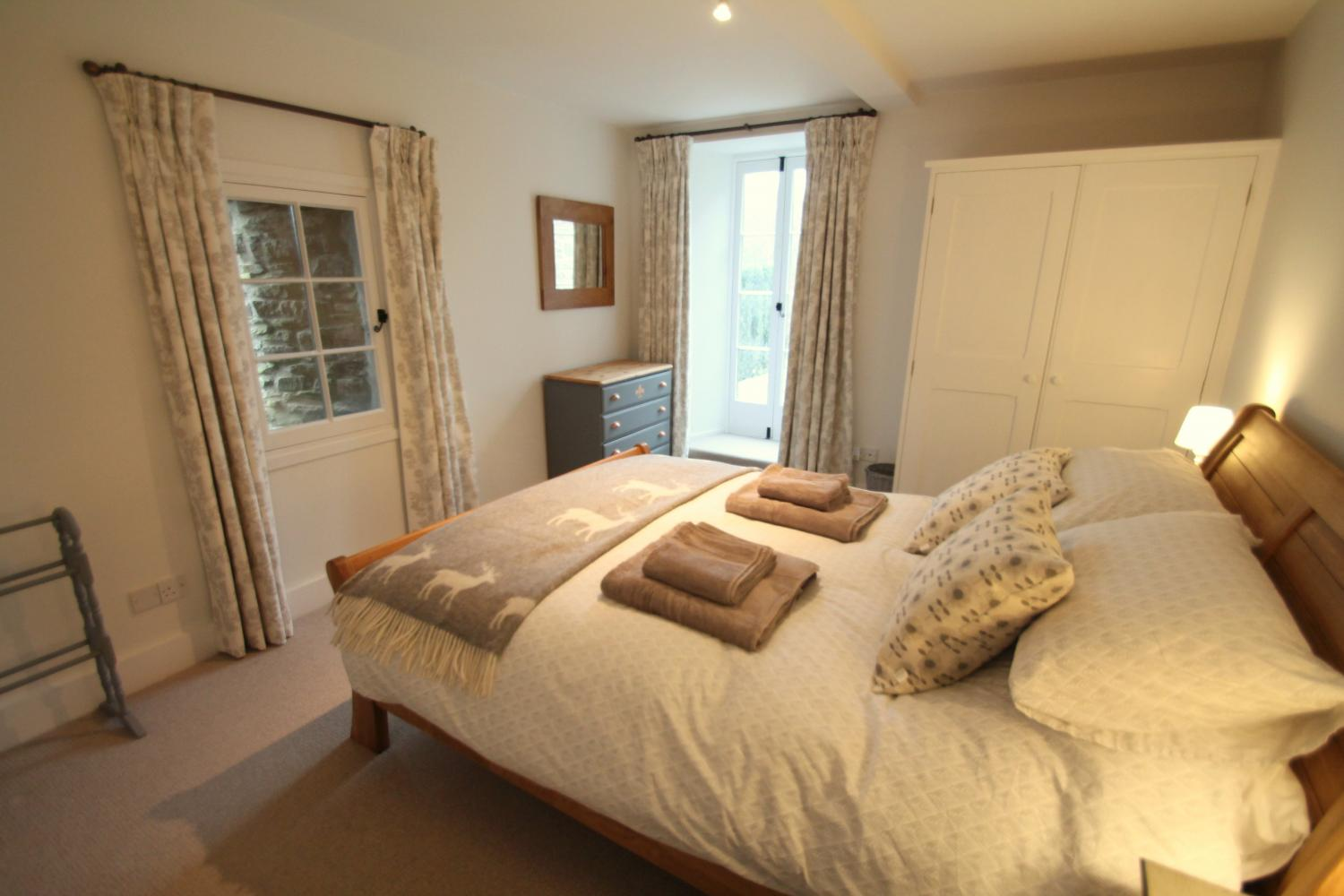 The ground floor master bedroom with king size sleigh bed and French doors onto the terrace.