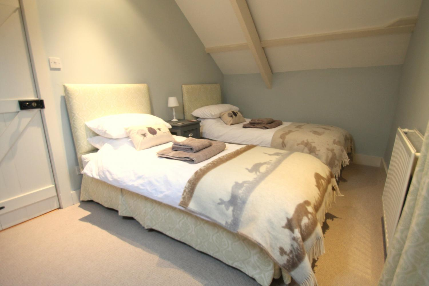 The twin bedroom is perfect for children or adults alike, and has views South out over the Devon countryside.